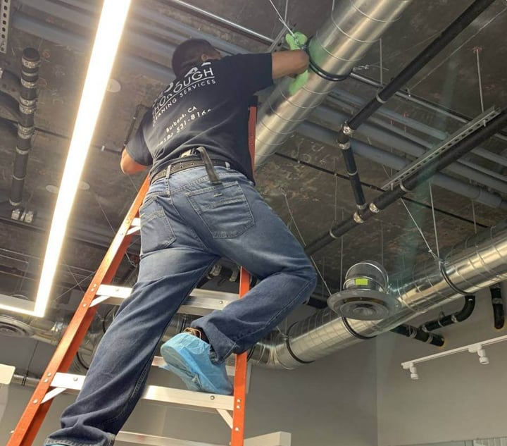 A Bluwolf service technician on a ladder wiping down an air duct